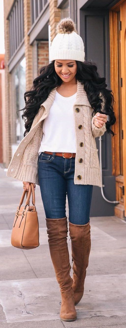 gray cable knitted jacket, white shirt, and blue-washed jeans