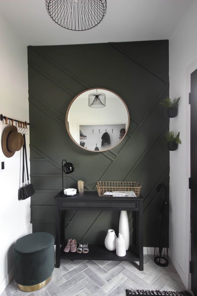 This gorgeous modern entryway reveal is here! What a huge transformation from the outdated space it once was! From the beautiful bench, to the herringbone floors, to the black front door, and the wood accent feature wall. This entry is stunning! #entryway #modern #entry #renovations #mudroom