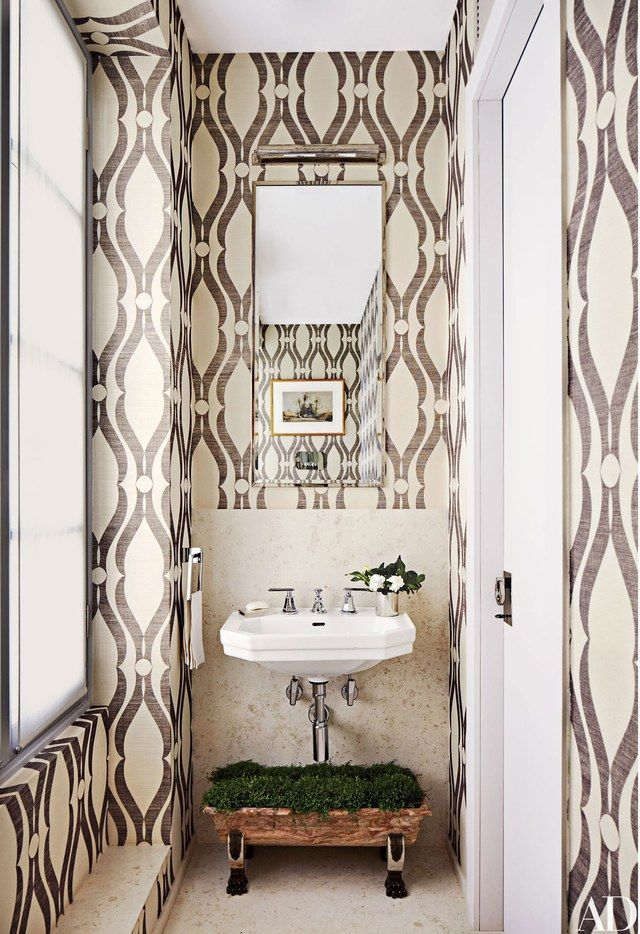 The powder room of a house in Monte Carlo designed by Timothy Whealon features Phillip Jeffries wallpaper and Dornbracht fittings.