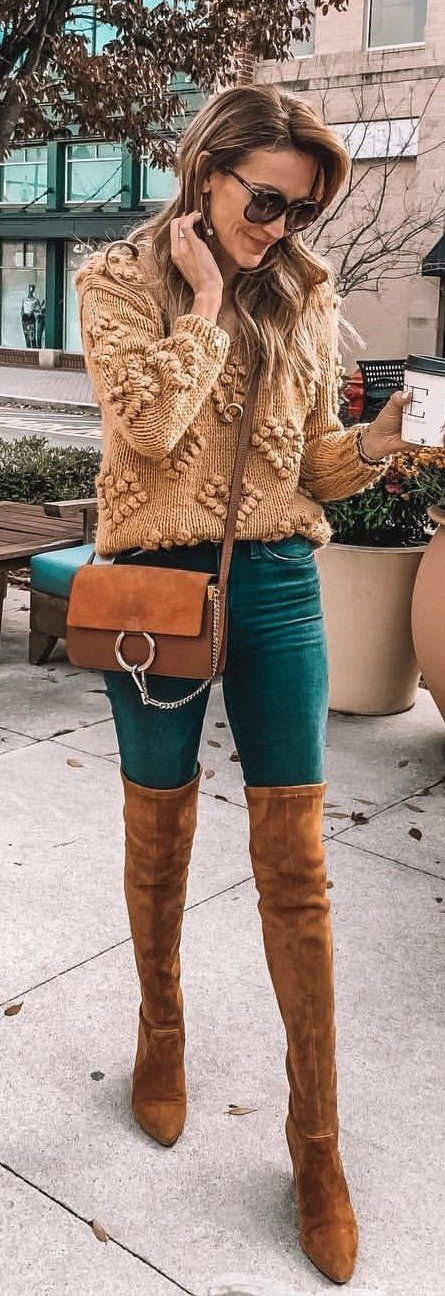 brown sweater, blue denim pants, and brown leather thigh-high boots outfit
