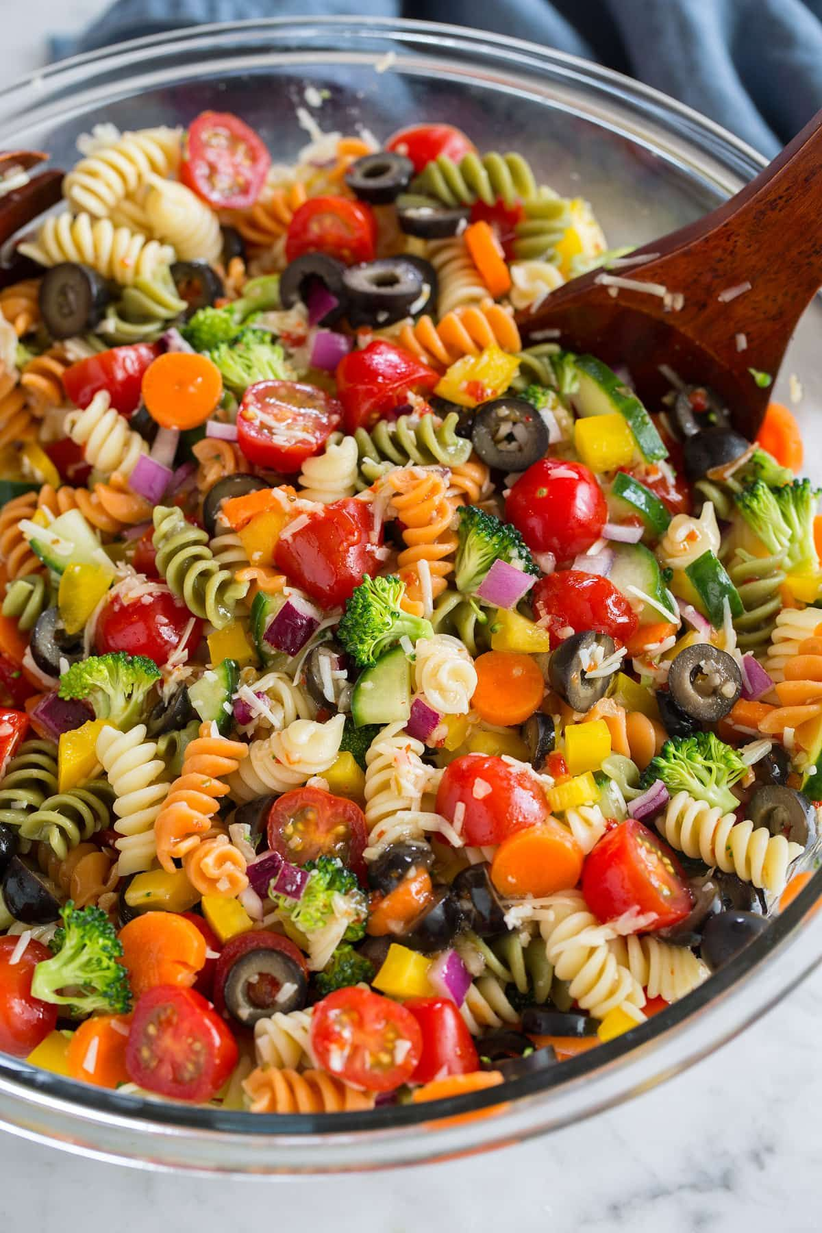 Pasta Salad is one of those staple recipes that's been around for as long as we can remember, and for good reason — it's amazingly delicious! This veggie packed version is easy thanks to the shortcut of zest bottled Italian salad dressing. #pasta #potluck #pastasalad #salad #sidedish #vegetarian #easy #familyfriendly