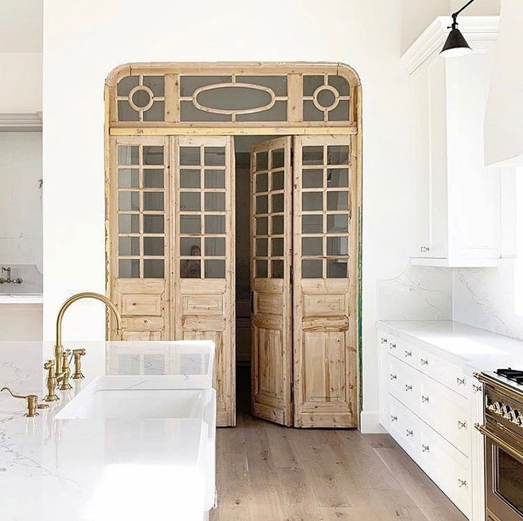 I'm loving this amazing kitchen design idea! Absolutely love the decor and how the statement wood french doors anchors the space while the pretty white cabinets and brass faucets gives a nice pop of color and texture!