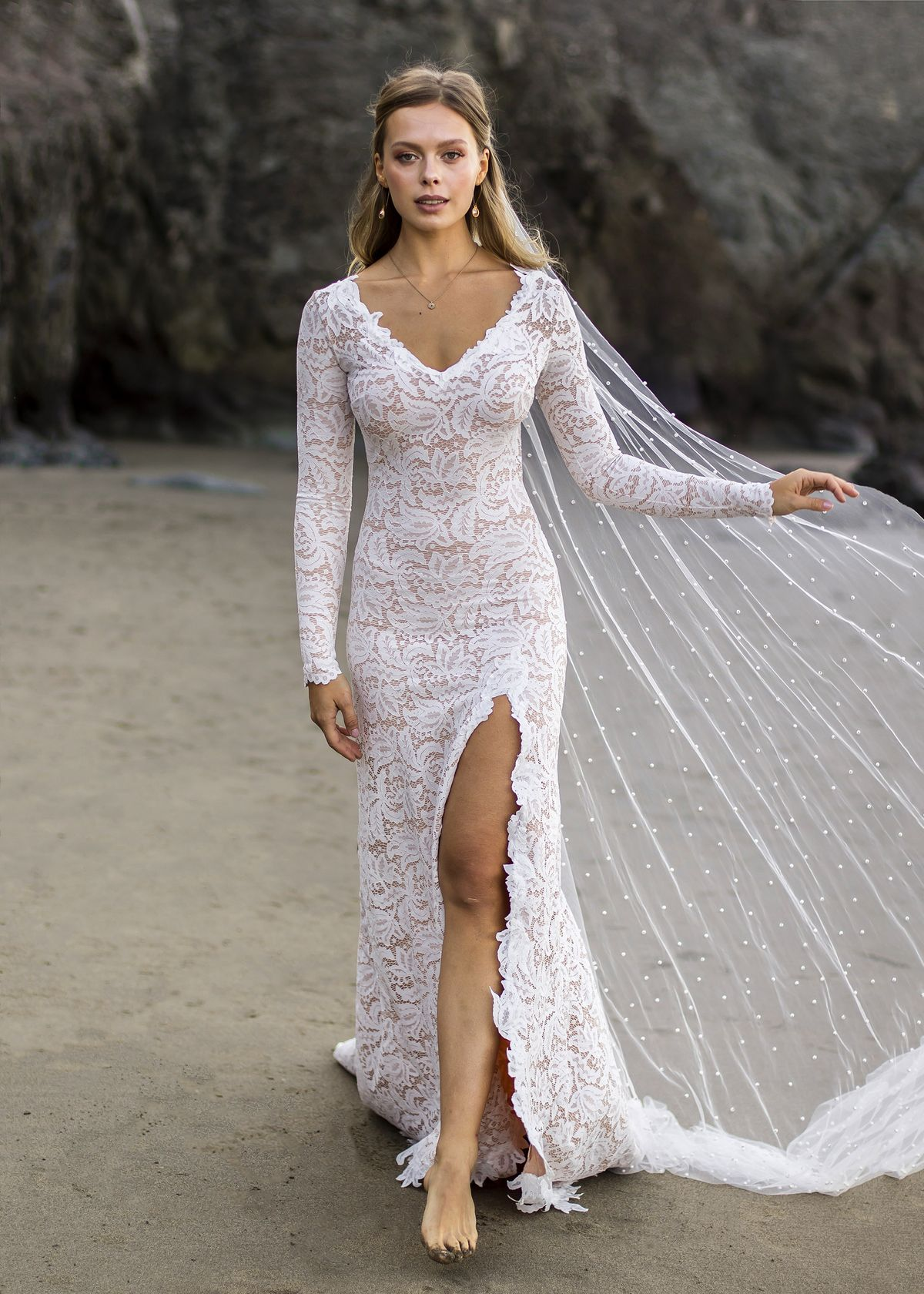 Salty haired brides are finding cannot get enough of this sexy stretch lace wedding dress with a daring high slit and scalloped hems. Hand crafted for every bride according to her individual measurements, this beloved style by Wear Your Love is once again on the up + up. Check this gown out in action on #ruffledblog!