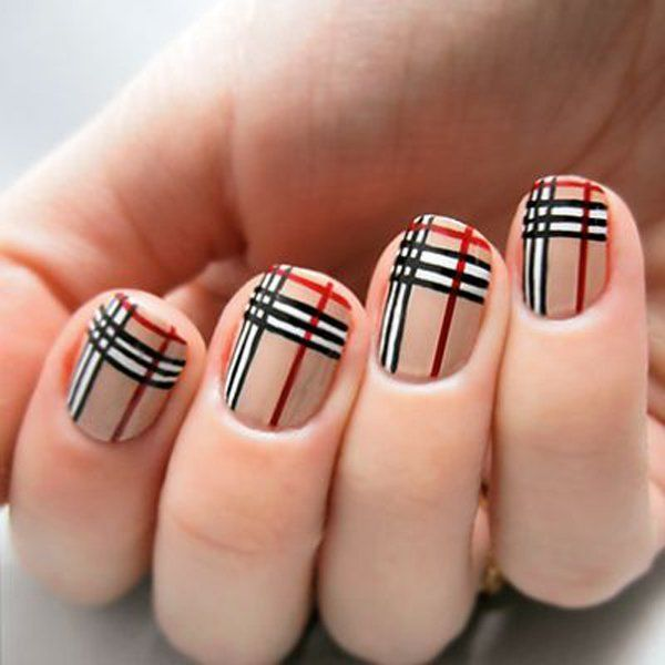 A uniform and clean looking plaid nail art design. The nails use nude color as base coat while adding black, white and red strips across and over the base color to complete the plaid design.
