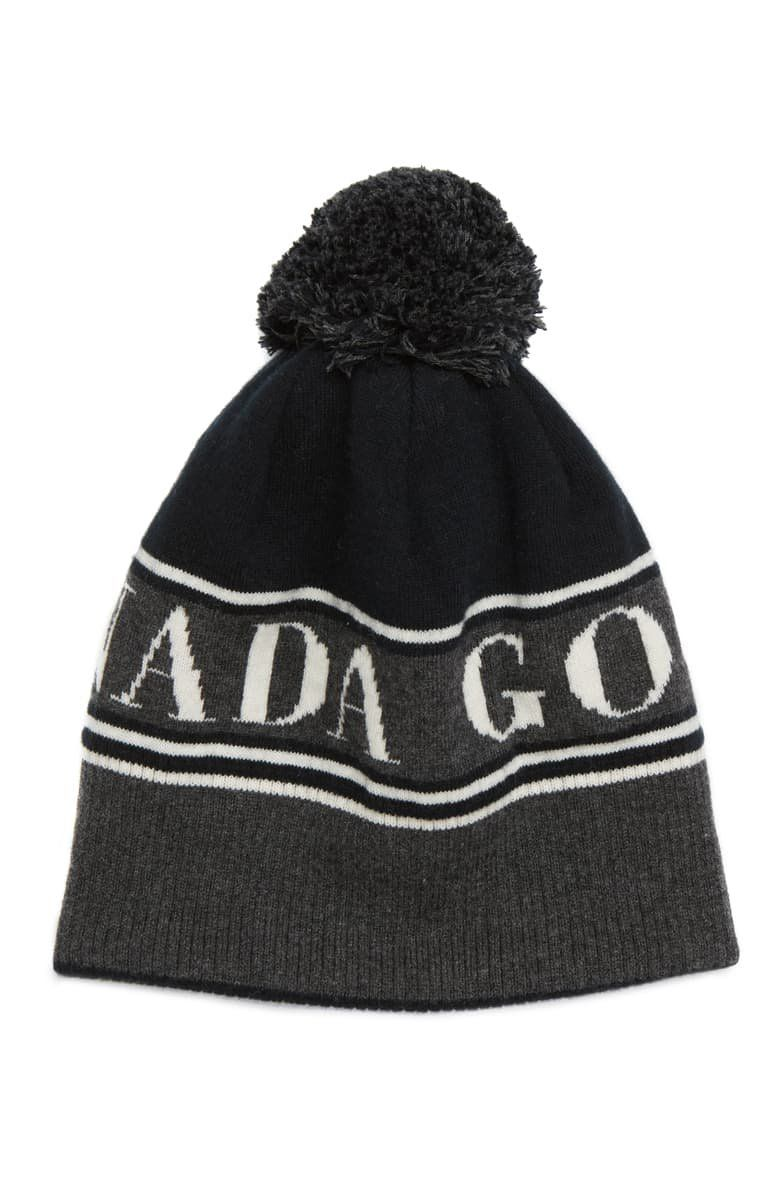 A cozy merino wool toque beanie is made in a chunky knit and topped by a fun pompom.