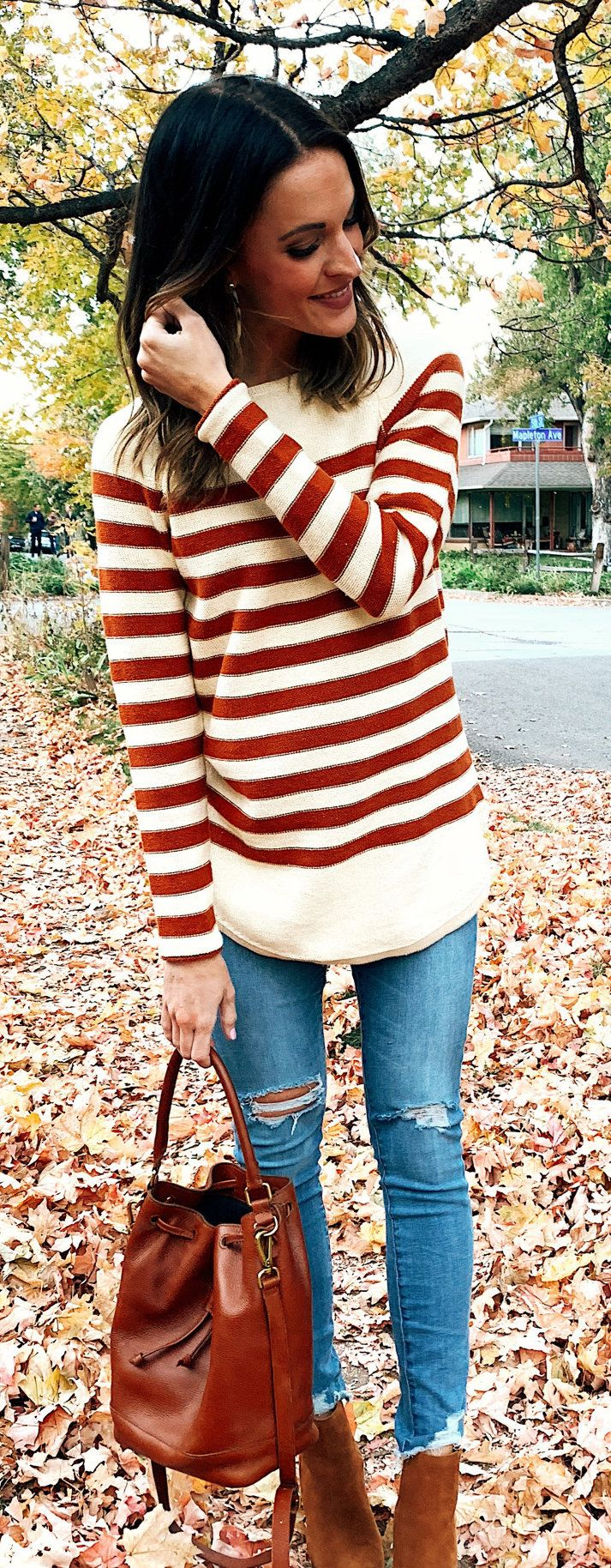 red and gray striped sweater and distressed blue-washed jeans