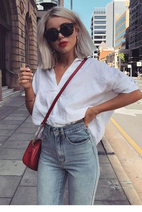 White oversize shirt and vintage jeans with a red bag