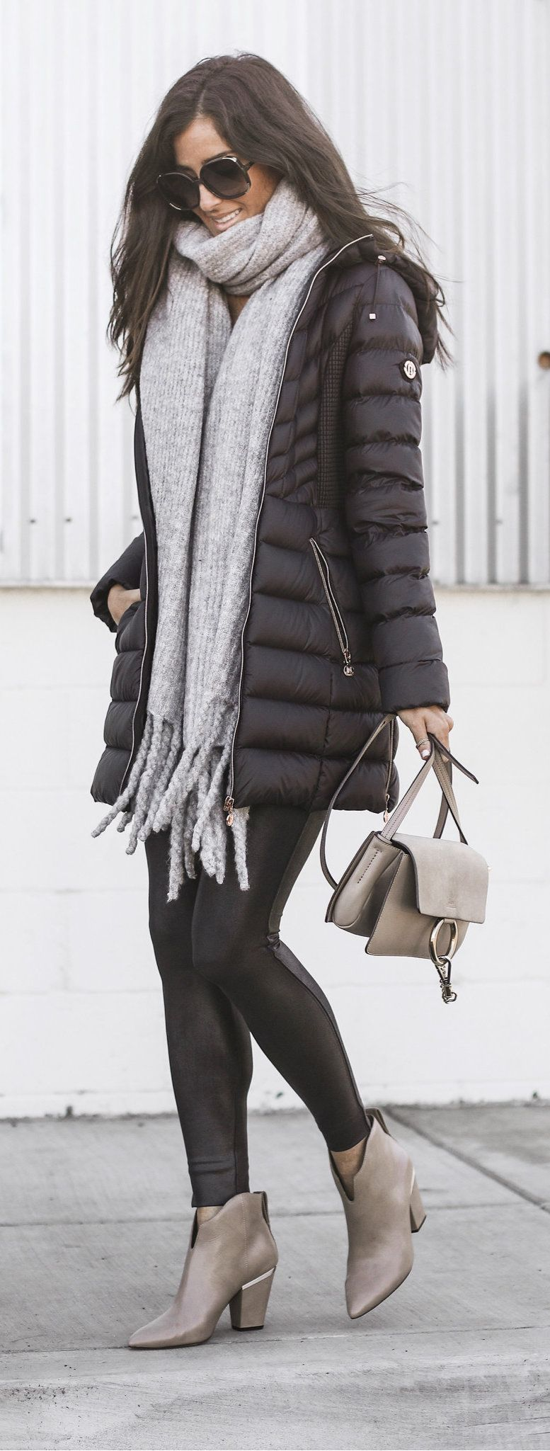 black zip-up bubble jacket and fringe gray scarf
