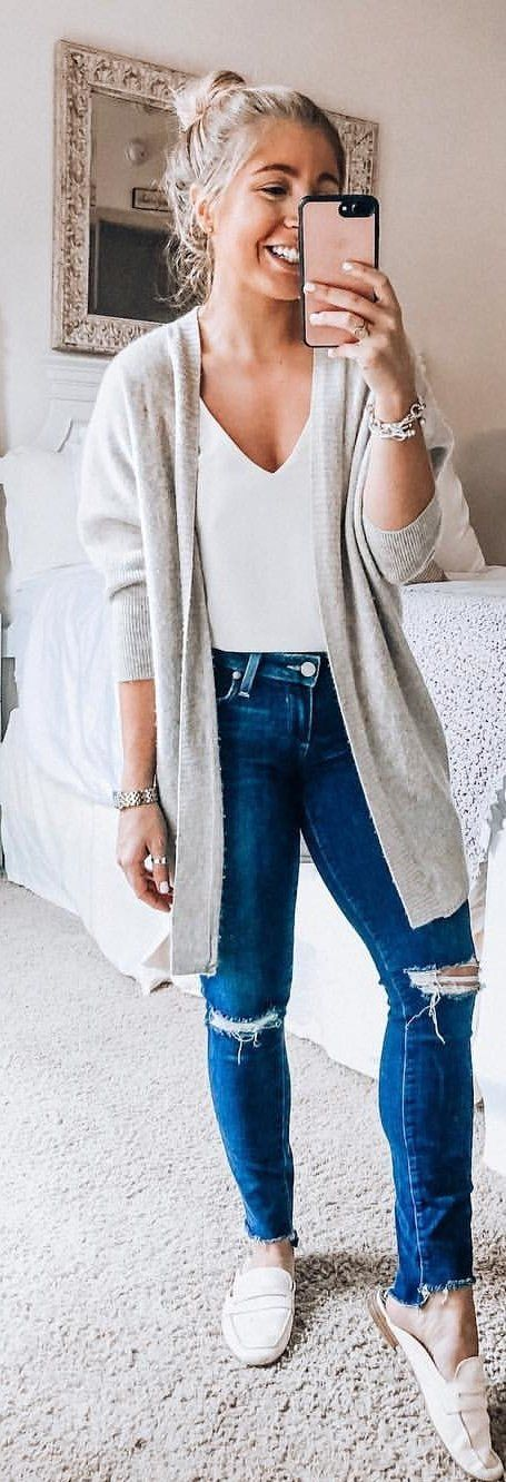 gray blazer, white V-neck top, and blue jeans