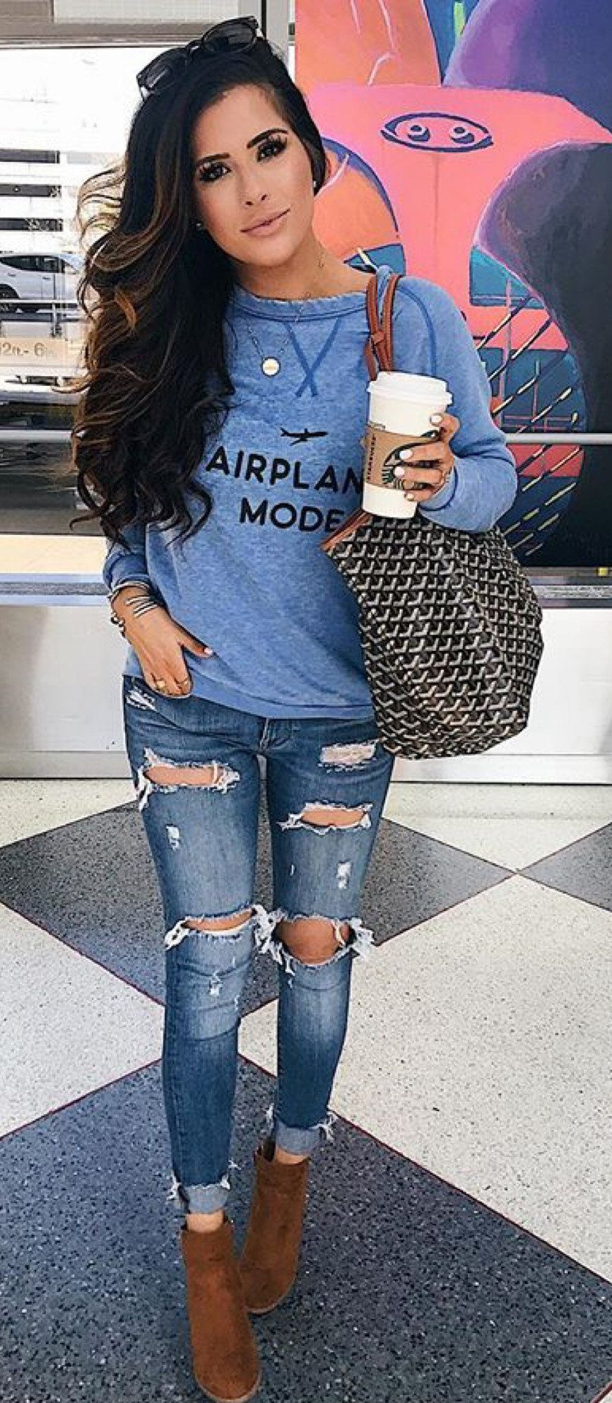 blue long-sleeved shirt and distressed faded blue jeans