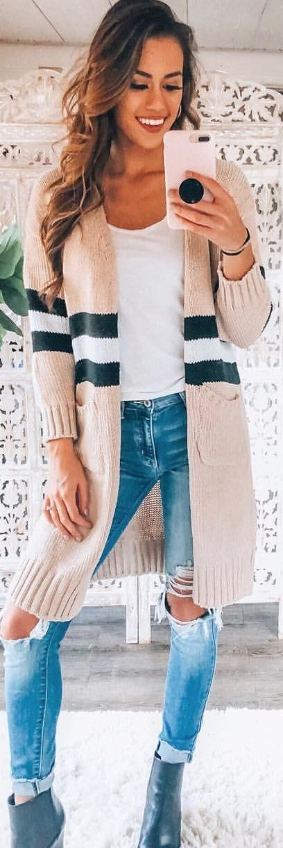 beige and black striped long-sleeved top and distressed blue jeans