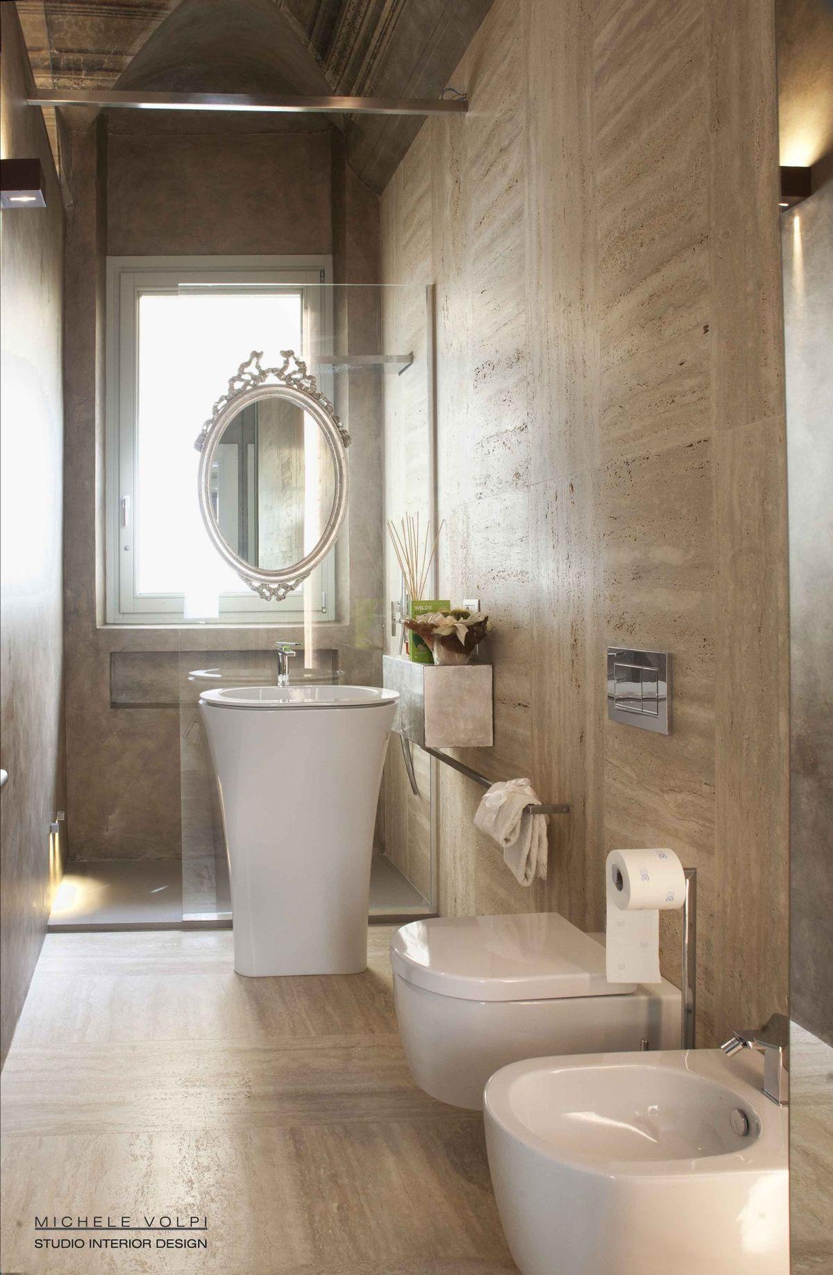 Un bagno in travertino e resina, uno specchio che sembra
