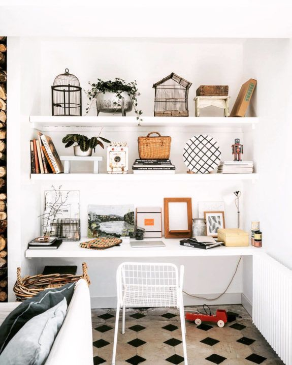 home office with white shelving styled by @zoedelascases with fun mix of vintage birdcages, paintings, and books. #birdcages #vintage #collection #tilefloor #desk #workspace #homeoffice #deskchair #desk #styling #shelves #shelving #storage #shelfie