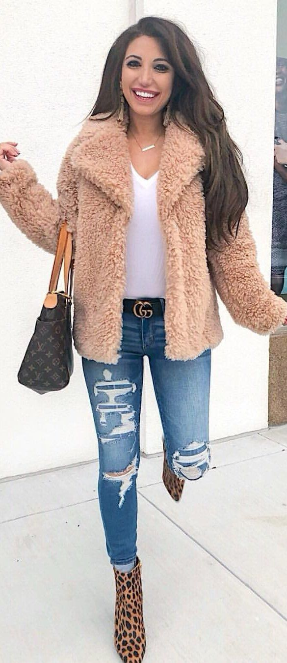 brown winter jacket and distressed blue denim jeans