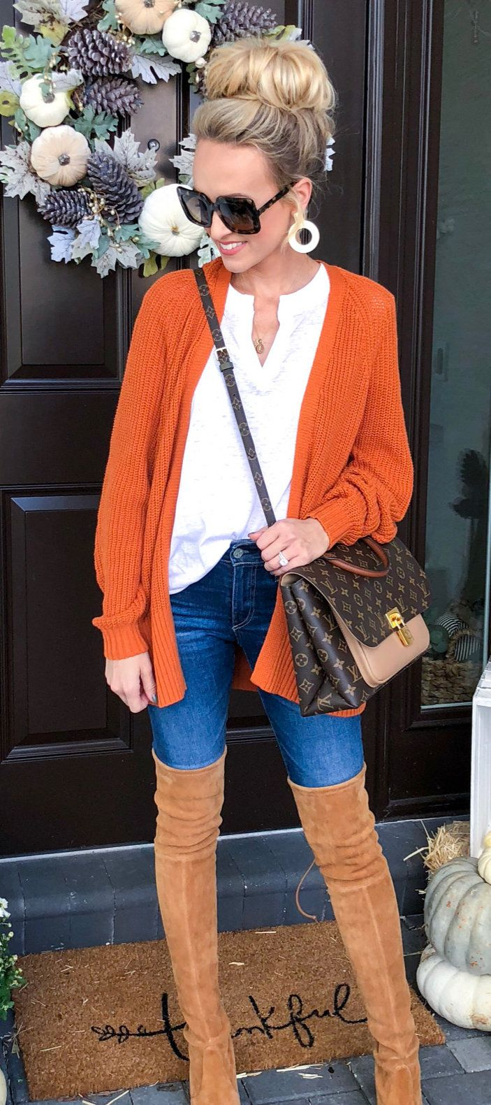 white V-neck shirt and orange cardigan