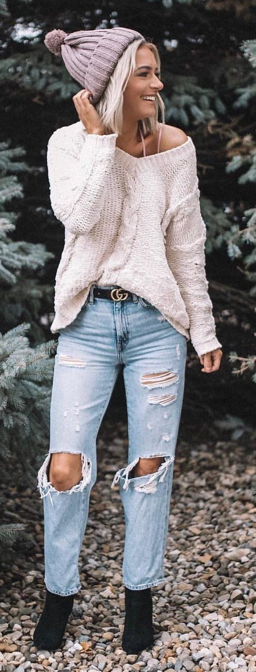 white sweater, distressed jeans, pair of black booties, and gray knit hat