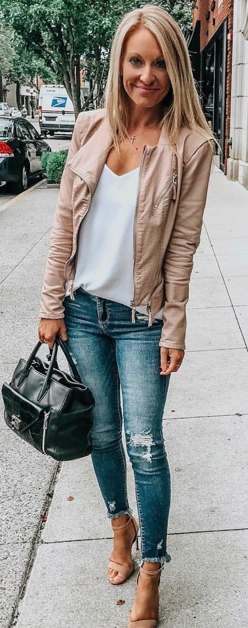 brown leather jacket, white top, blue skinny jeans, and pair of sandals