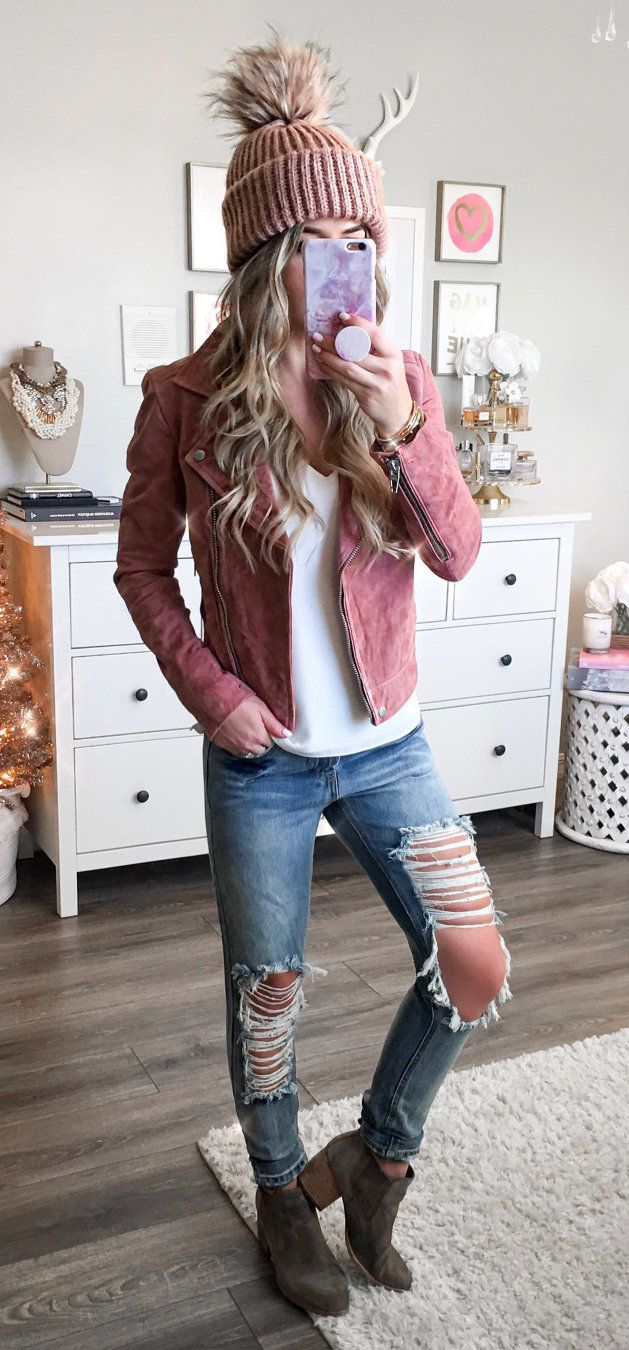 women's pink suede zip-up jacket and distressed blue-washed jeans with red and brown bobble head and pair of brown platform heeled mid-calf boots. Click To Shop This Look.