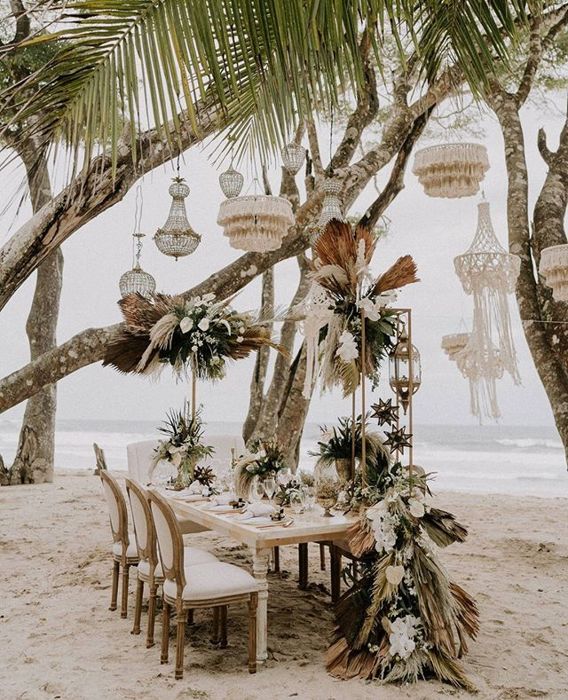 Hello paradise! I don't think we'll ever recover from such a gorgeous setup. This intimate coastal elopement in Costa Rica features crystal chandeliers and hand-woven macrame lamps and the prettiest dried botanicals. #ruffledvendor photo @rawshoots planner lettering @eventos.oneheart venue @haciendabarrigona video @forever.wf @loveathand florals @dianapalomofloraldesign rentals @dgalaevents @deco_73 dress @elky_suarez suit @fabrizzioberrocal hair makeup @tamarasabatemua @roberthquiros_ f