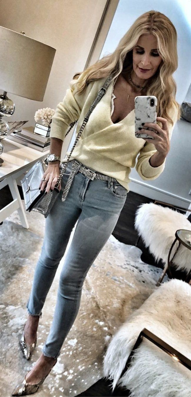 beige V-neck sweater and blue denim jeans. #spring #outfits