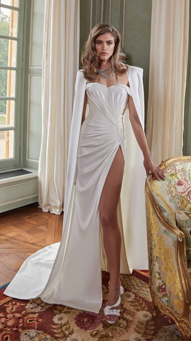 Like light bouncing off of a brilliant diamond – our new Fancy White Fall 2020 bridal collection is elegant, beautiful and dramatic – just look at #Anna our silk satin, glass-like column wedding dress expertly draped by hand – featuring a thigh high slit and sexy off-the – shoulder straps. For added drama wear down the aisle with the pleated shoulder, silk satin cape.