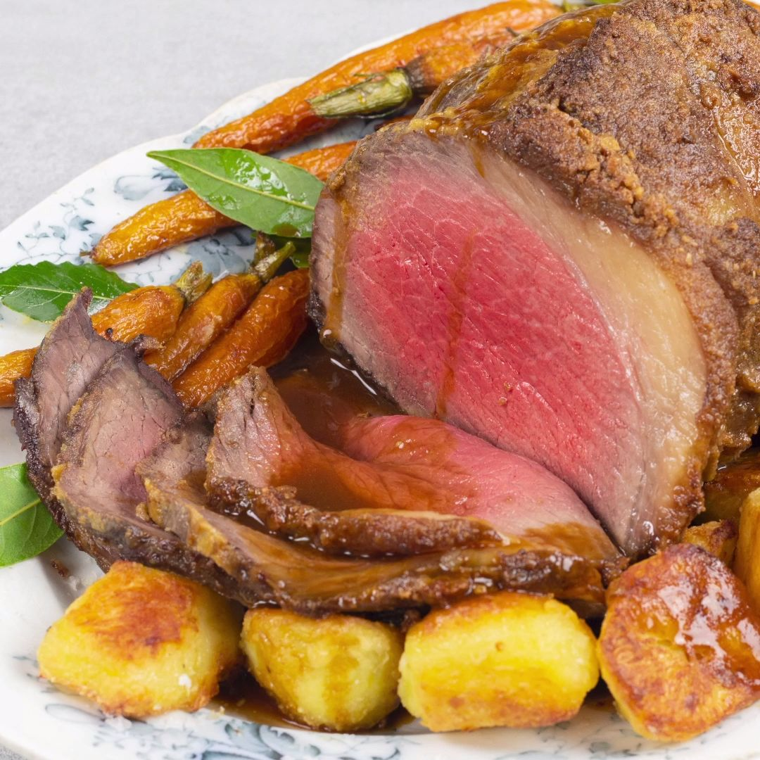 Roast topside of beef with crispy potatoes and gravy.