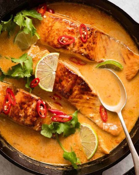 Poached Salmon in Coconut Lime Sauce in a black skillet, fresh off the stove ready to be served