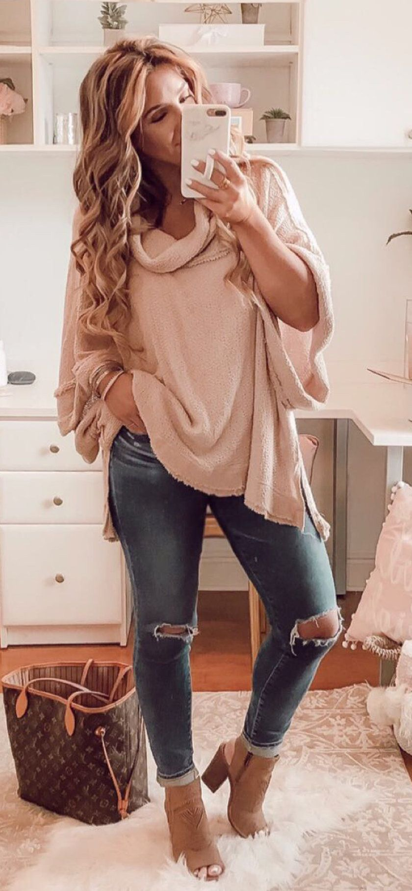 blue distressed jeans and beige long-sleeved top