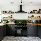 Kitchen makeover with dark grey units, palm print wallpaper and green accents