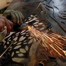 10 inch Photo. A worker uses an angle grinder on a piece of