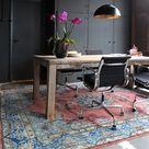 Grote houten tafel met fantastisch kleed en zwarte inbouw kasten.