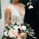 Swoon worthy wedding details. This muted earthy wedding bouquet pairs back beautifully to this plunging V-neck A-line wedding dress with floral appliques. This beautiful boho wedding dress is by Melissa Sweet and available at David's Bridal   Photo by Bethany Small Photo