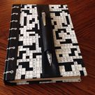 Loose cover for a crossword book. Secret Belgian Binding with leather spine, crossword fabric over mat board and a leather pencil holder/bookmark with elastic to hold it in place.