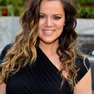 Khloe Kardashian long curly hair in dark blue dress