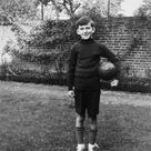 Box Canvas Print. Boy standing in garden with rugby ball,