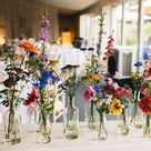 Colourful wild flowers in bud vases.