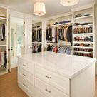 Stunning walk-in closet with floor to ceiling shelving and clothes rails and a center closet island.