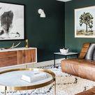 dark green walls contrast warm brown leather furniture and make the living room ...