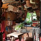 Cosy clutted country kitchen with pans and wicker baskets hung from...
