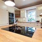 Moderne Landhausküche in weiß von Häcker Küchen mit Kochinsel, BORA Kochfeld und NEFF Elektrogeräten - Küchenhaus Thiemann Overath/Vilkerath