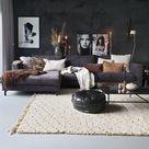 een zwarte hoekbank, zwarte muur en veel grijstinten