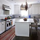 Beautiful kitchen features a wood chandelier hanging over a center island topped with white marble lined with gray Wishbone Barstools facing a stainless steel hood over a Wolf Range.