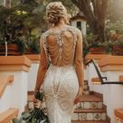 A bride wore a see through wedding dress with a keyhole back covered in vintage looking crystals