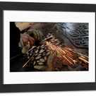 Framed Photo. A worker uses an angle grinder on a piece of metal