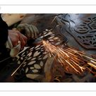 25cm Photo. A worker uses an angle grinder on a piece of metal