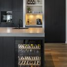 Zwarte keuken met kookeiland en wijnklimaatkast