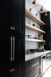 black cabinetry with gold colored harware and accents, light wood shelving