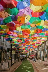 Inspo from our friends! Águedas Umbrella Sky Project began in 2011 as a part of the Portuguese citys annual Ágitagueda Art Festival. Each summer, when temperatures soar, a handful of Águedas narrow streets feature canopies of colorful umbrellas that provide shade to the pedestrians bel