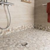 Un sol de carrelage beige imitation galet pour la douche dans la salle de bain