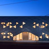 Tessellating windows and cladding panels create a pattern of triangles on the facade of this …